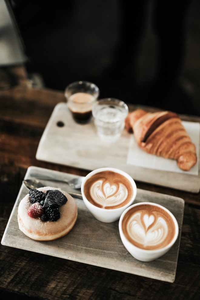 table with coffee and pastries on top